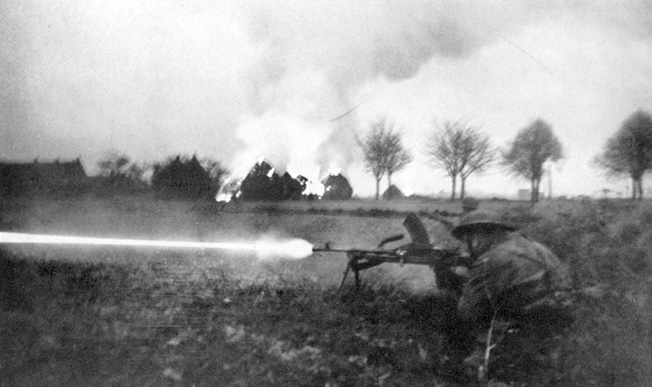 A British soldier fires a Bren gun in an open field near Arnhem as haystacks blaze in the background. Less than 2,000 members of the British 1st Airborne Division escaped capture or death during Operation Market-Garden. Relief forces failed to arrive in time to secure the bridge across the Lower Rhine.