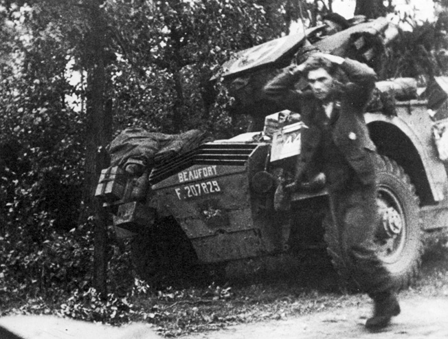 A German soldier surrenders to members of the British Guards Armored Division during the drive to relieve Arnhem.
