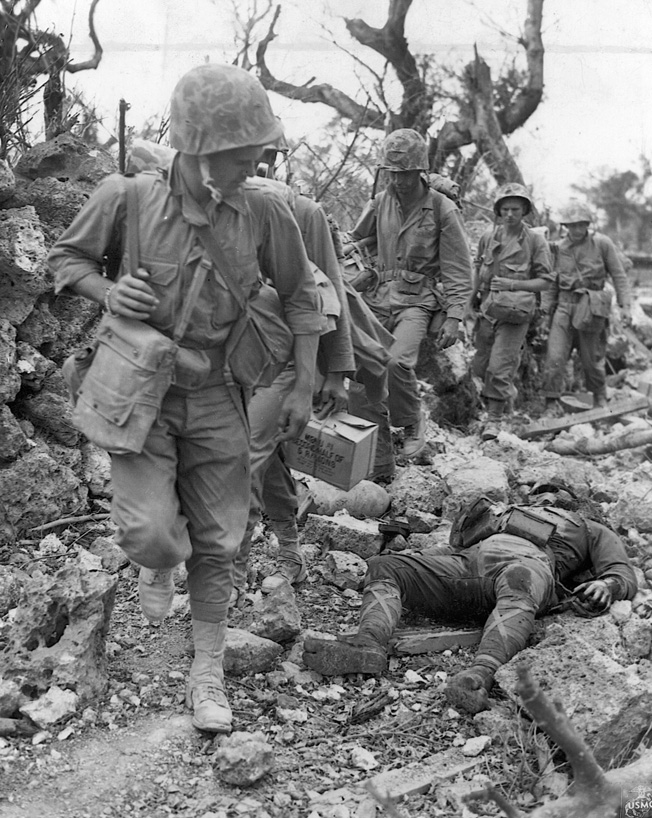 Pressing forward, U.S. Marines glance at the body of a dead Japanese soldier on May 24, 1945. At the time this photo was taken, another grueling month of fighting and dying remained before Okinawa was declared secure.
