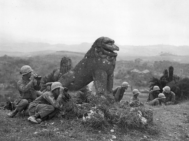 A battered Okinawan statue shows the effects of recent shellfire while observers of the U.S. 7th Infantry Division use it as partial cover.