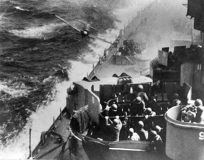 Gunners aboard the battleship USS Missouri work feverishly to take a diving Japanese kamikaze under fire. During the Battle of Okinawa. U.S. naval forces were repeatedly subjected to attacks by enemy suicide planes.