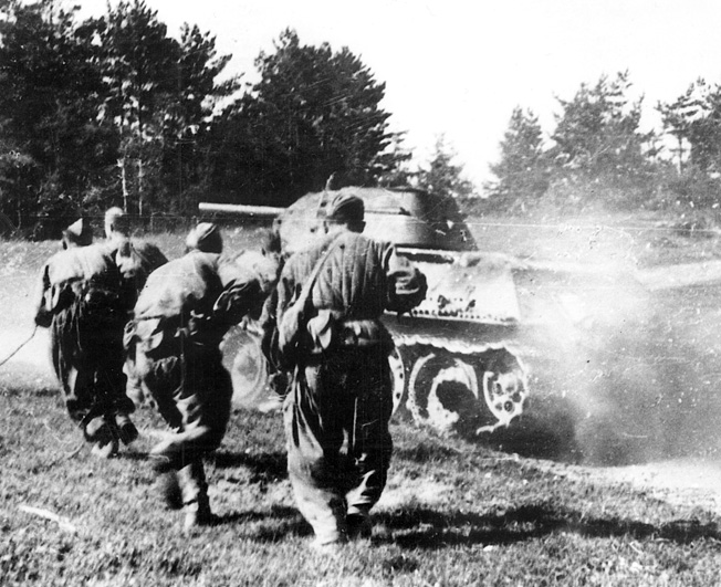 An advancing T-34 tank stirs up a cloud of summertime dust as Red Army soldiers crouch behind it. The Soviet armed forces mounted a devastating offensive in 1944, which carried them to the gates of Berlin.