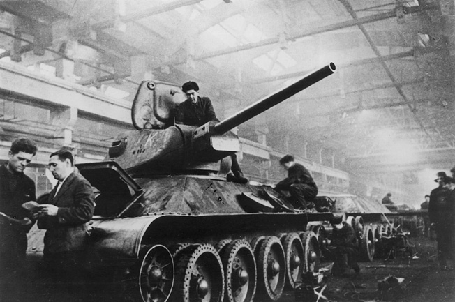 Workers make final adjustments to the turret and chassis of a new T-34 medium tank. Many of these stalwart fighting vehicles were driven straight from the factory into combat.
