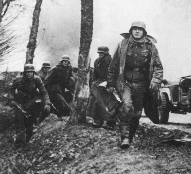 German troops stride past flaming American vehicles during the Battle of the Bulge. The soldier in the foreground carries a Mauser Kar 98 rifle, while the one at left holds a StG44 assault Rifle.