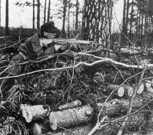 In action against the advancing Allies on the Western Front, a Waffen-SS soldier takes aim with a Sturmgewehr 44 assault rifle during the waning months of World War II.