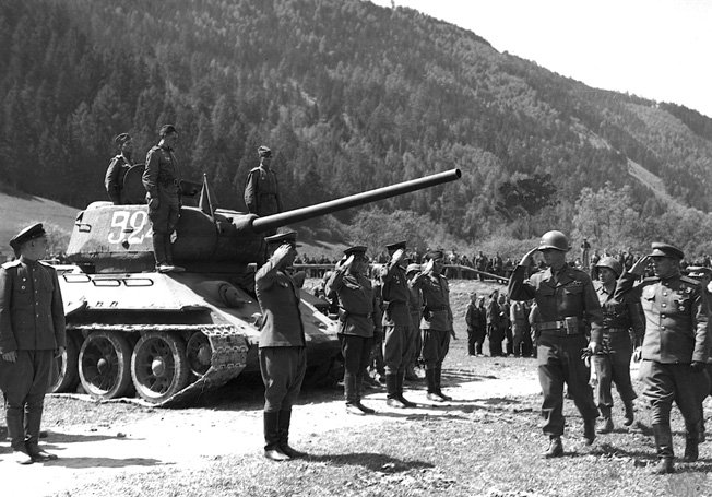 A detachment of Red Army Guards snaps to attention as a group of visiting Americans passes. A T-34 tank squats with the Soviets on a parade ground after the end of hostilities.