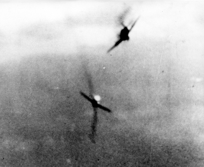 Locked in deadly combat, the guns of a Navy Hellcat rake a Japanese Zero during an aerial encounter above the Marianas.