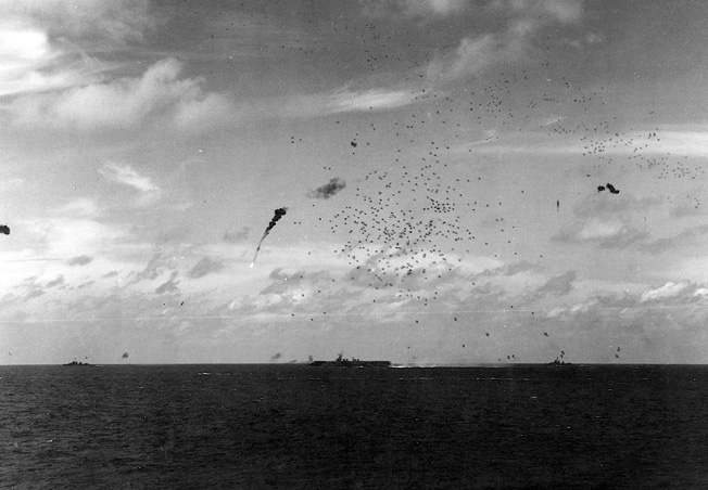 A Japanese plane bursts into flames as accurate antiaircraft fire from an American escort carrier sends it spiraling into the sea.