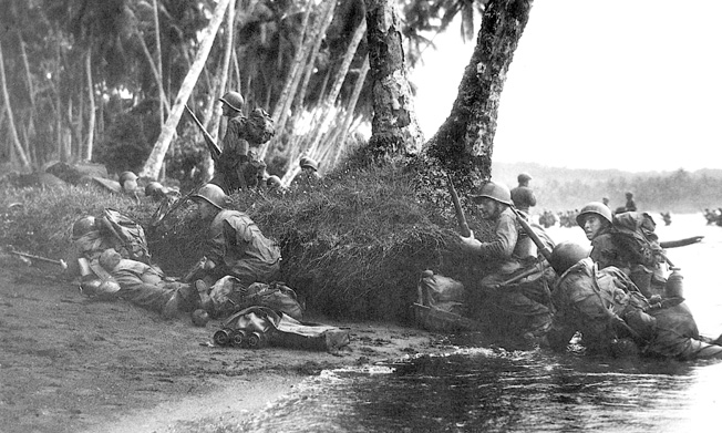Attacking at the break of day in a heavy rainstorm, the first Marines ashore take cover behind tree trunks and and anything else they can find.