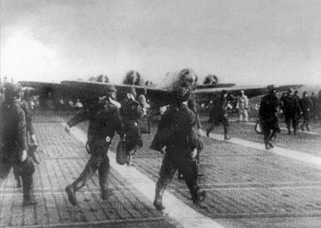 Japanese pilots rush to their planes. This photo is probably of the second wave, as the first wave took off in darkness.