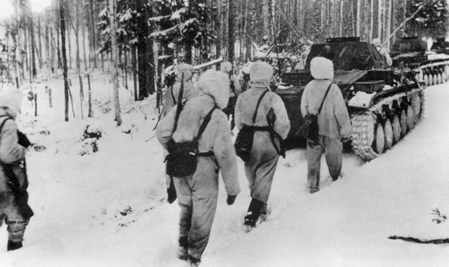 Marching toward Moscow in late 1941, German soldiers camouflaged in white for winter fighting trail armored vehicle along a route of advance.