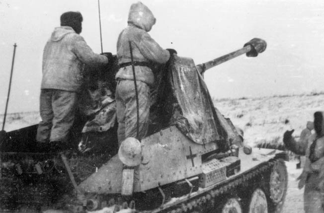 "A self-propelled Sd.Kfz 138 Marder III assault gun of the 2nd SS Division ""Das Reich"" rolls into position during the winter of 1941-1942 as two crewmen stare across the vast, frozen landscape."