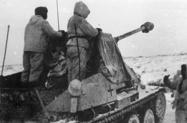 A self-propelled Sdkfz 138 assault gun of the 2nd SS Division Das Reich rolls into position during the winter of 1941 as two crewmen stare across the desolate, frozen landscape of Russia.