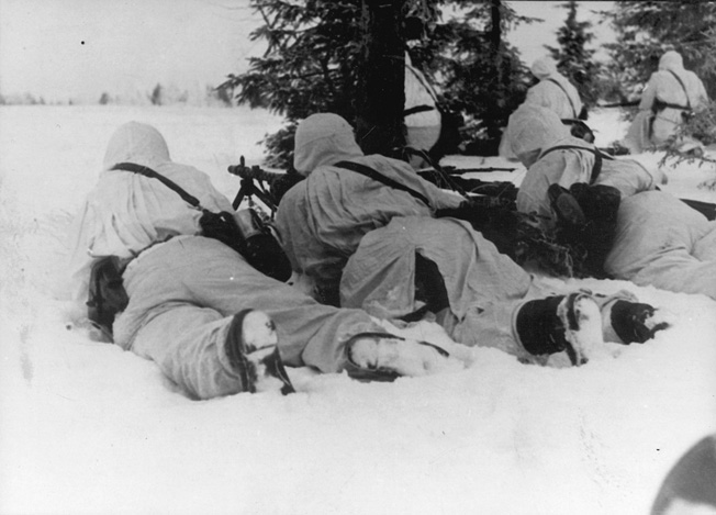 German machine gunners, camouflaged for winter warfare, scan an open field for targets. The vanguard of the Soviet offensive near Rzhev ran into a determined defense mounted by crack troops of the elite SS.