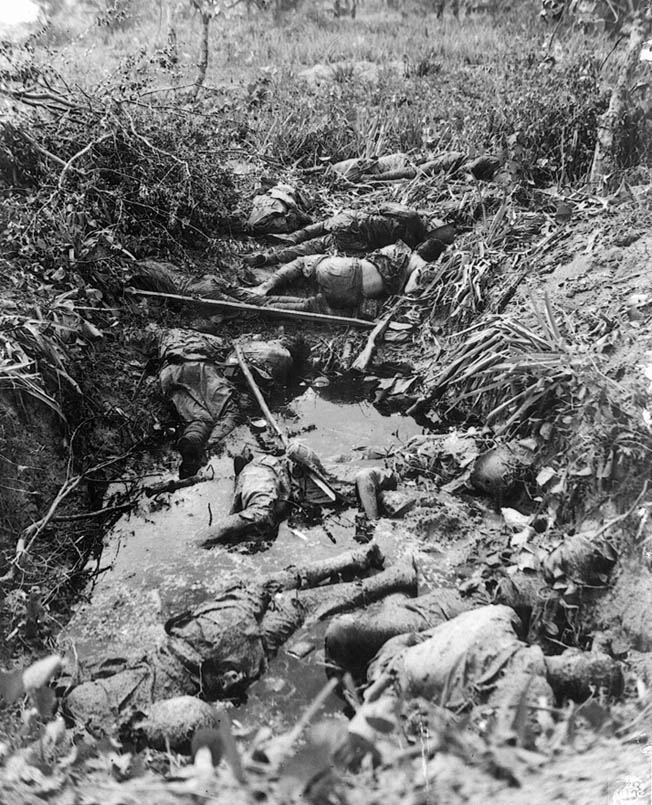 A half dozen dead Japanese occupy a water-filled shellhole, giving mute testimony to the savagery of the fighting.