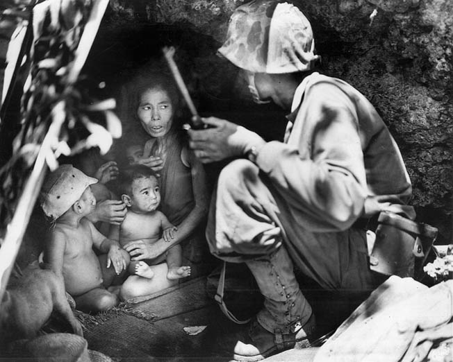 A Marine finds a woman and her children in hiding. Many of the civilians, believing Japanese propaganda, were so fearful that the Americans would torture them that they committed suicide in droves.