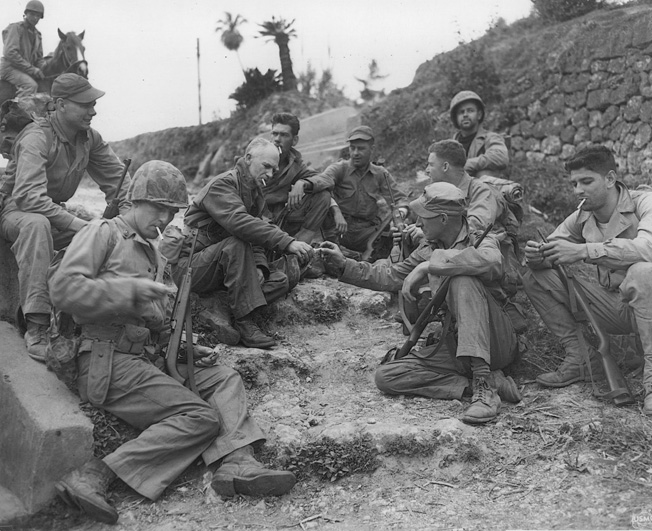 On April 18, 1945, only days before his death, famed war correspondent Ernie Pyle shares cigarettes with a group of Marines from the U.S. 1st Division on the wartorn island of Okinawa.