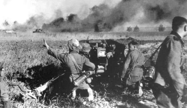 During the desperate fighting in the summer of 1941, a German antitank gun engages Soviet armor on a desolate Russian plain. Smoke from the ongoing battle shrouds the horizon while German tanks roll.