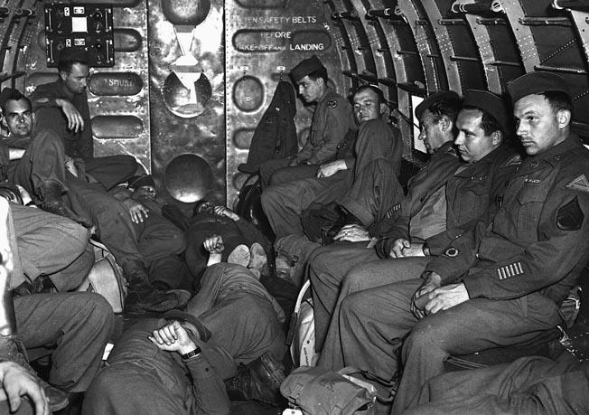 U.S. military personnel endure a long flight home aboard a Douglas C-47 in June 1945.