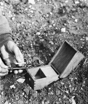 A wooden pressure sensor to detonate a remote TNT mine.