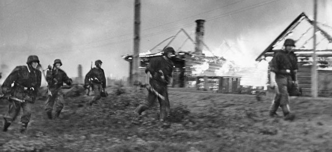 German troops rush past burning houses as they sweep through a Russian village during the early days of Operation Barbarossa, the invasion of the Soviet Union that commenced on June 22, 1941. In an ironic twist, the Soviets allowed German infantry and armored units to train secretly inside the Soviet Union during the interwar years, violating of the Treaty of Versailles.