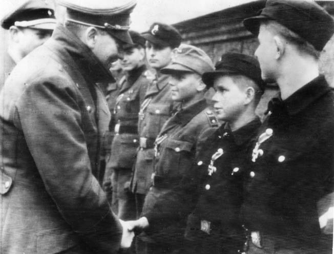 During one of Hitler's last public appearances, he presents the German cross to a 12-year-old boy for heroism in action against the Soviets approaching the capital of Berlin.