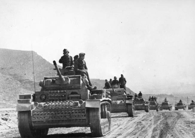 A column of German PzKpfw. III tanks rolls down a dirt road in Tunisia. Battle groups such as Kampfgruppe Fullriede proved effective in the field with armor, artillery, and infantry working in concert. Although intended as temporary combat formations, they often endured extended periods on the front lines.