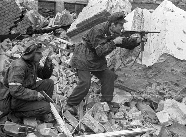 "Members of Anna Company of the Gustaw Battalion, Home Army soldiers Henryk Ozarek ""Henio"" (left), holding a Vis pistol, and Tadeusz Przybyszewski ""Roma"" (right), firing a Błyskawica submachine gun, battle the hated Germans on Kredytowa-Królewska Street in Warsaw. This photo was taken on October 3, 1944."