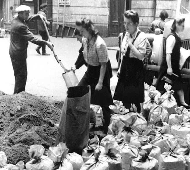 Residents of Warsaw hurriedly fill sandbags to erect a barricade on Moniuszki Street in August 1944. The Warsaw Uprising was heroic but futile as the Germans crushed the resistance with overwhelming firepower.