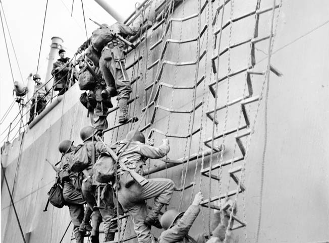 Clattering down rope ladders with full equipment, American soldiers board a landing craft for the invasion of France. Bob Watson thought this kind of training irrelevant until D-Day.