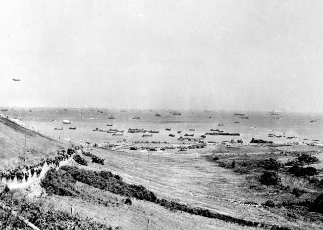 The Colleville Draw was the widest of the five draws on Omaha Beach. Bob Watson escorted enemy prisoners from a pen that would have been to the bottom right of the photograph. Various ships and landing craft deliver supplies and take away prisoners and wounded soldiers.
