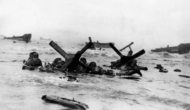 """Under fire, American soldiers and sailors crawl up the beach near the Colleville Draw through enemy obstacles. The man on the left wears a Navy engineer helmet with a white inverted """"U."""" Bob Watson wore a similar helmet, except his """"U"""" was orange."""