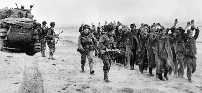 While a tank rolls forward, American soldiers escort German prisoners of war to a waiting ship. Note the gas mask bag on the chest of the center soldier. Soldiers had to wear them for the first seven days on the beach.