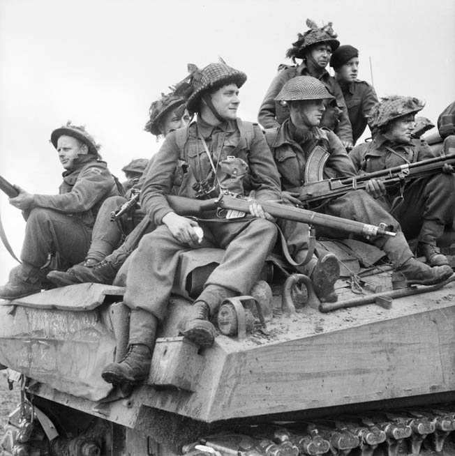 British soldiers riding on a Sherman tank clutch their Lee-Enfield rifles as they advance into Holland during Operation Market Garden. A scarcity of funds and an abun- dance of rifles and leftover ammunition from World War I compelled the British to distribute the improved SMLE No. 4 Mark I to their soldiers in World War II.