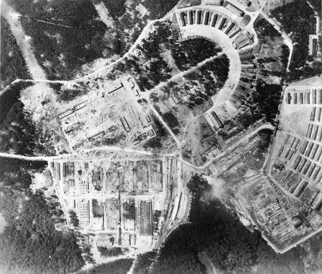 Air Force bomb-damage assessment photo taken after Mission 132 shows that the factory has been completely destroyed, while the prisoner enclosure to the right sustained only minor damage.