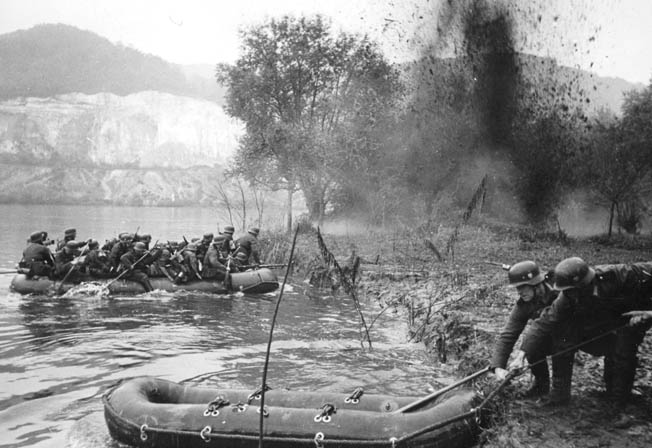 German troops use inflatable rubber rafts to cross the Meuse River while under fire.