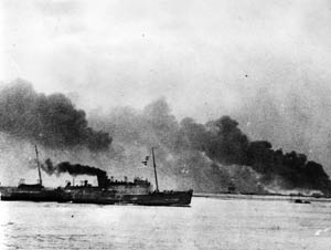 Filled with evacuated troops, a British ship departs the smoke-shrouded Dunkirk beach area during Operation Dynamo, June 1940.