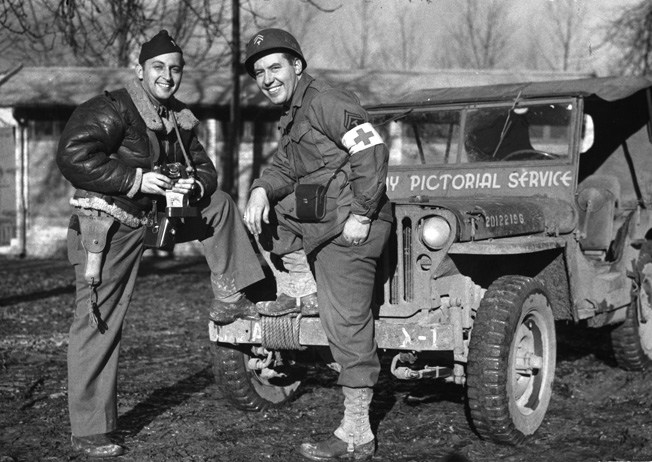 Lieutenant WIlliam Wilson chats with a medic. Note the jeep windshield frame that says it belongs to the Army Pictorial Service.