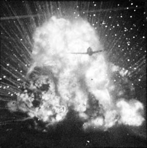 As a German truck loaded with ammunition explodes in a fireball, an American P-47 fighter flies through the flames, smoke, and debris.