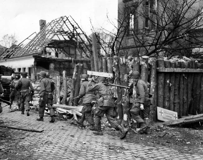 Men of Company C, 513th PIR, fighting with the U.S. Ninth Army, pass through a roadblock in Münster, northeast of Wesel, April 1, 1945.