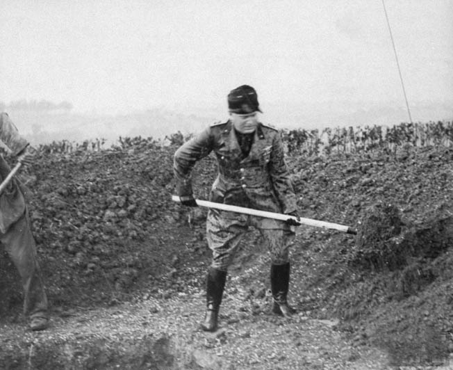 As part of the ground-breaking ceremonies in 1938, Mussolini plants a tree.