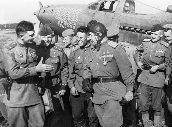 His P-39 emblazoned with victory stars stands in the background as Soviet fighter ace Alexander Pokryshkin talks with ground personnel after returning from a mission against the Germans on the Eastern Front during World War II.