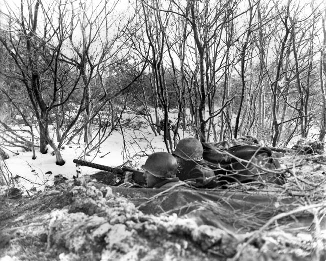 Men of the 157th Regiment operate a M1919 Browning heavy machine gun from their foxhole, December 1944. Besides a stubborn enemy, the winter weather took its toll on the attackers.