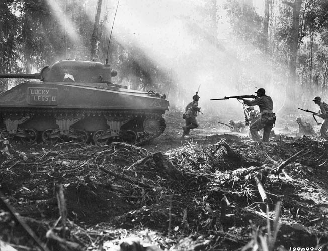 Sunlight streams through the jungle canopy as soldiers of the 129th Infantry, 37th Division, supported by a Sherman tank, battle Japanese infiltrators on Bougainville, March 16, 1944.