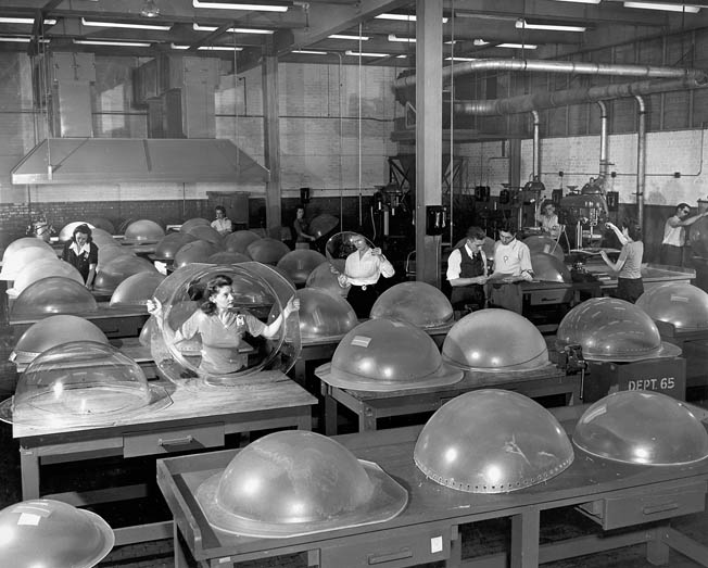 "Employees inspect plexiglass ""blister"" dome win- dows. The B-29 was produced at four factories around the United States."