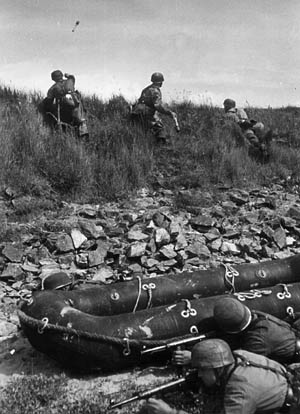Fallschirmjäger throw Model 24 stick grenades at U.S. forces near Carentan. German paratroopers wore little equipment during operations; only weapons and ammunition were carried, with perhaps an additional field bag and canteen.