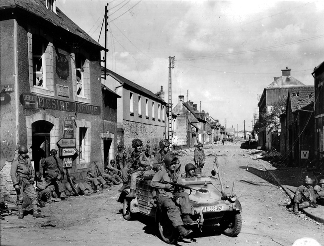 American paratroopers ride a captured Kubelwagen at the crossroads of the Rue Holgate and RN 13 in Carentan, June 12, 1944.