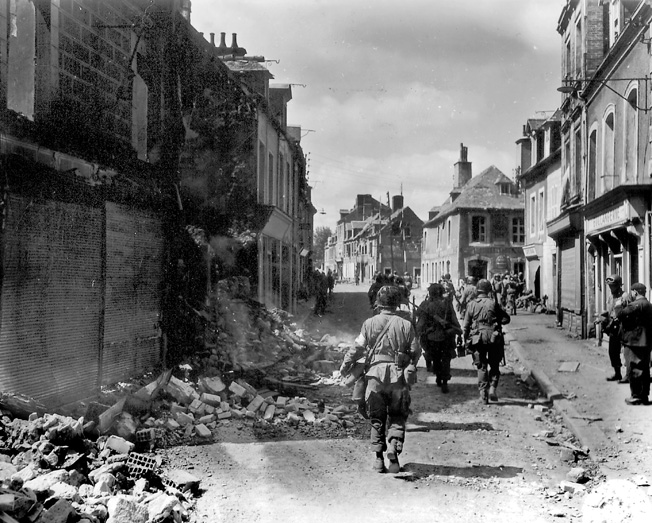 An American medic (possibly of the 326th Airborne Medical Company) and other 101st Airborne troops patrol along Rue Holgate in Carentan, June 12, 1944.