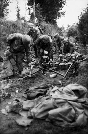 Fallschirmjäger gather weapons for a coming fight. The man in foreground is grabbing the tripod to a machine gun while the soldier behind him reaches for cans of machine-gun ammunition.