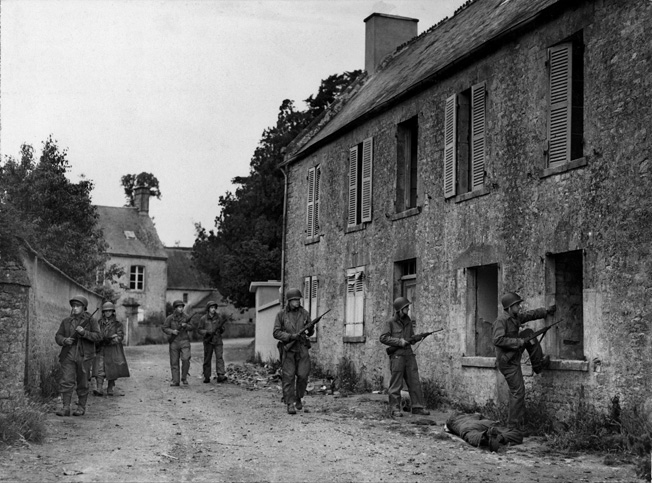 "American infantrymen who came ashore at Utah Beach go house to house in a Normandy village looking for Germans lying in ambush, June 1944. After the men of Fallschirmjäger Regiment 6 were forced to pull back from Ste.-Mère-Église to St.-Côme-du-Mont, they made a ""last stand"" at Carentan."